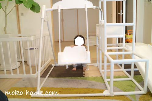 ホワイトカラーの室内用ジャングルジム・ブランコで遊ぶ子ども