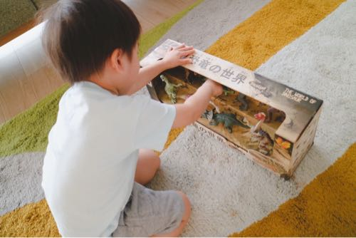 リアルな恐竜フィギュアセットを開ける3歳児